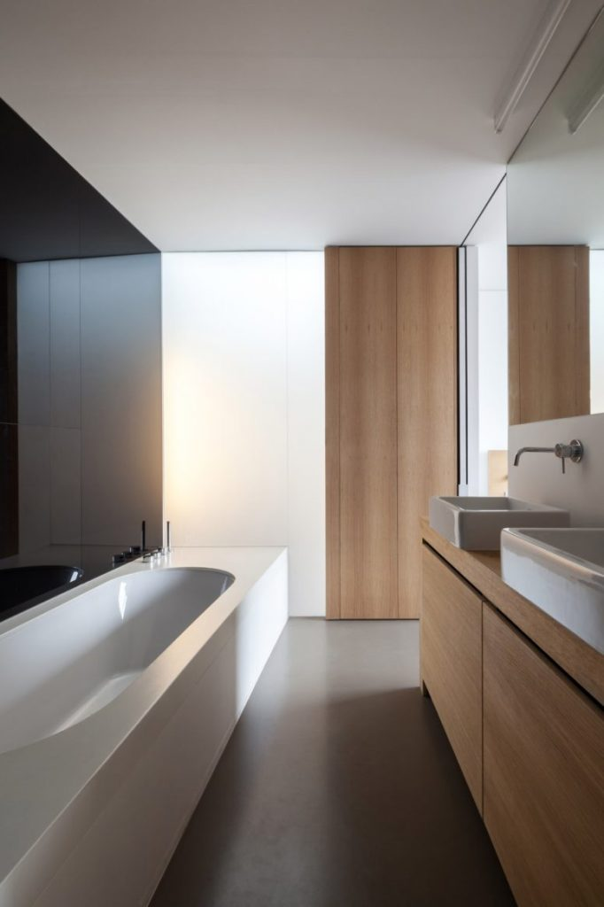 04-The-bathroom-features-warm-wood-panels-sleek-black-and-white-walls-and-a-modern-bathtub-775x1163