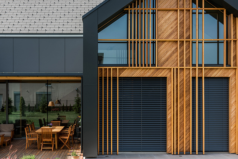 08-A-set-of-wood-cladding-adds-a-geometrical-composition-to-the-facade-and-gives-some-privacy-at-the-same-time