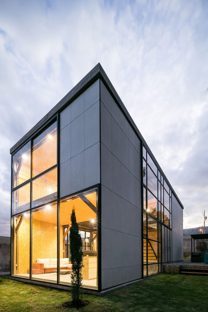 Simple-cement-panels-with-socket-joints-and-glass-windows-shape-the-multi-generational-home-in-Quito