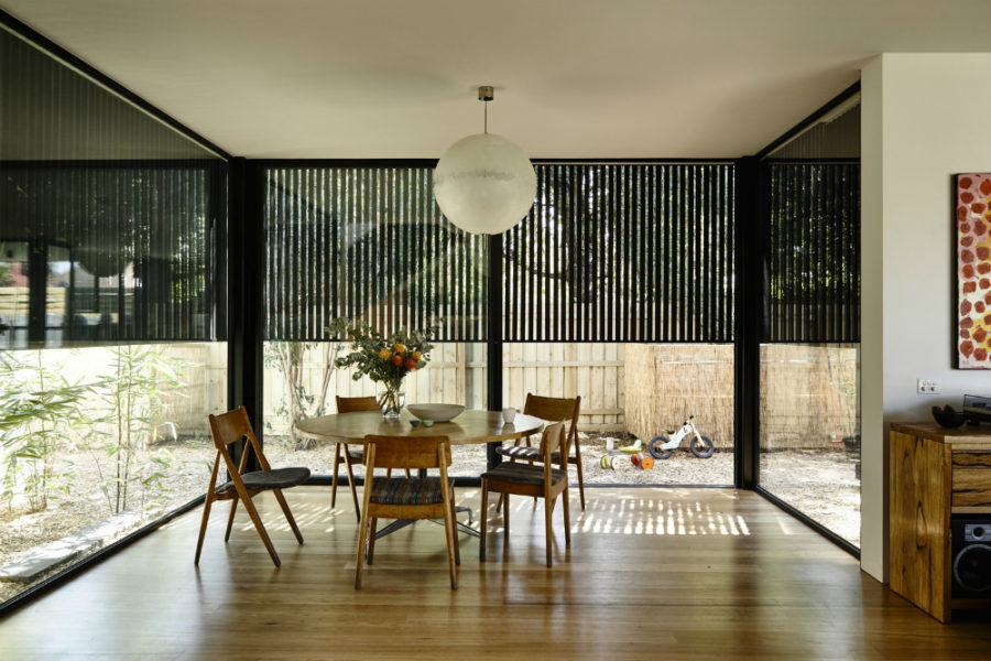 The-dining-area-partially-protected-with-a-black-wooden-screen-900x600